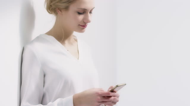 young woman using mobile phone against wall - leaning stock videos & royalty-free footage