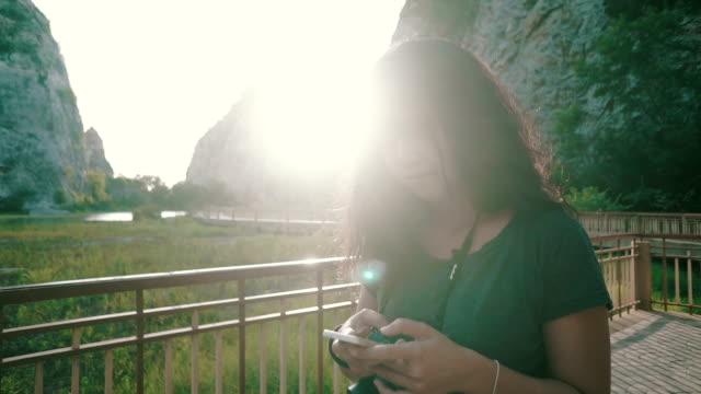 vídeos de stock, filmes e b-roll de jovem mulher usando telefone celular no parque - escandinávia