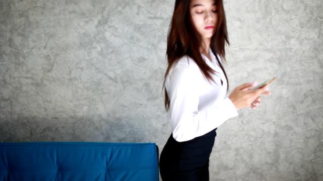 vídeos de stock e filmes b-roll de jovem mulher com telefone móvel - saia