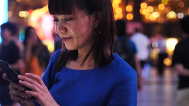 若い女性を使用して携帯電話街の美しいボケと - カッコいい点の映像素材/bロール