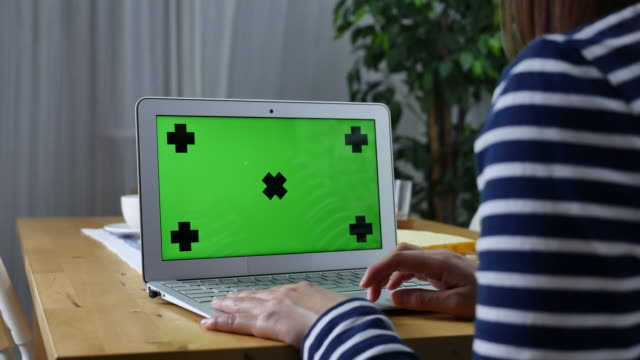 Young woman using on computer laptop with green screen,Dolly shot