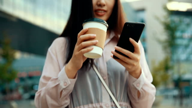 young woman using phone and drinking coffee - coffee drink stock videos & royalty-free footage
