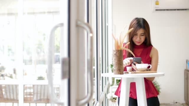 junge frau beim telefonieren im café - only young women stock-videos und b-roll-filmmaterial