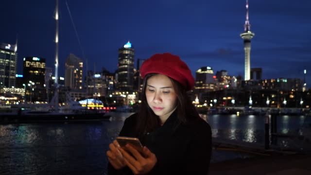 young woman using  phone at city night - only young women stock videos & royalty-free footage