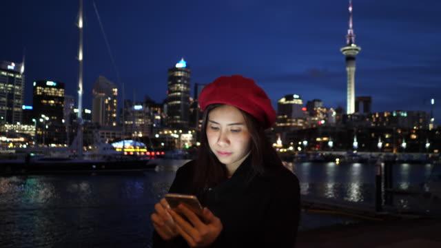 junge frau mit telefon in der stadt nacht - only young women stock-videos und b-roll-filmmaterial