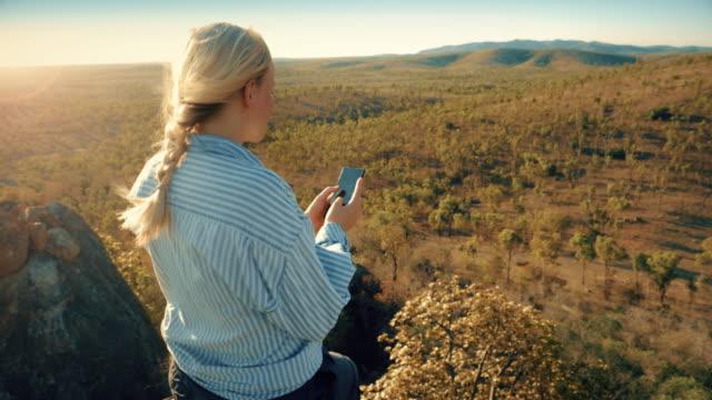 vidéos et rushes de jeune femme à l'aide de téléphone, des terres agricoles australiennes. - remote location
