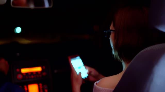 vidéos et rushes de jeune femme utilisant le téléphone pour la messagerie de la voiture - taxi