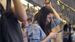 Young woman using phone for social networking on train, Slow motion