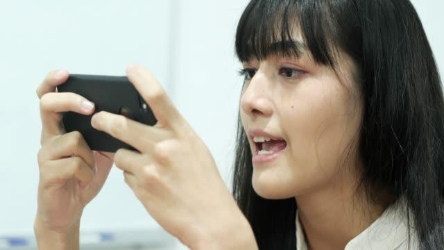 junge frau mit telefon für social networking - weibliche angestellte stock-videos und b-roll-filmmaterial