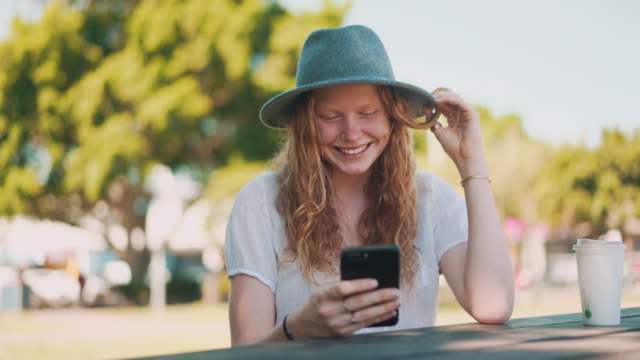 young woman using phone in a park - candid stock videos & royalty-free footage