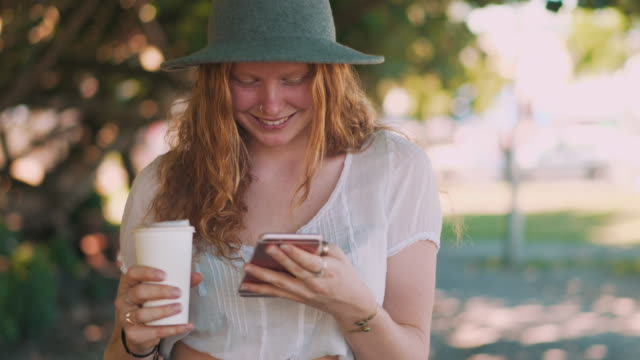 young woman using phone in a park - redhead stock videos & royalty-free footage