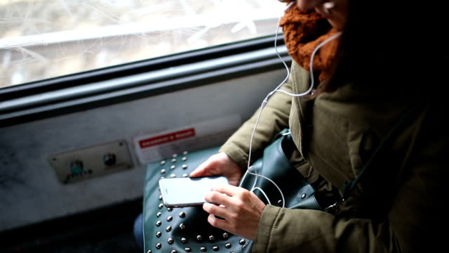 young woman using phone in public transportation - scrolling stock videos & royalty-free footage