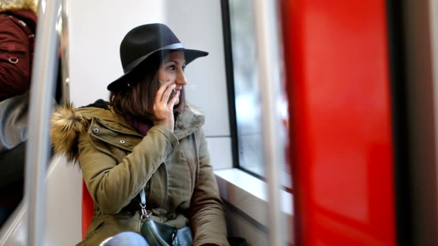 Young woman using phone in the bus