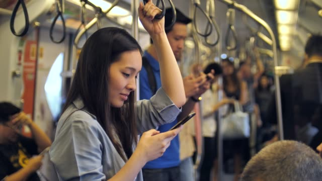 young woman using phone on metro subway - public transportation stock videos & royalty-free footage