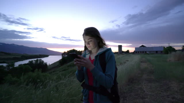 vídeos y material grabado en eventos de stock de ms young woman using phone while hiking on mountain - footpath