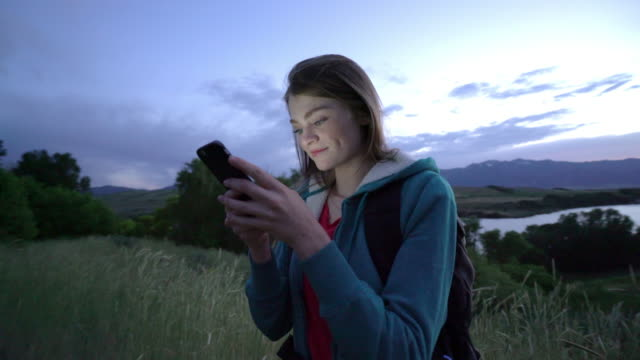 vidéos et rushes de ms young woman using phone while hiking on mountain - 10 secondes et plus