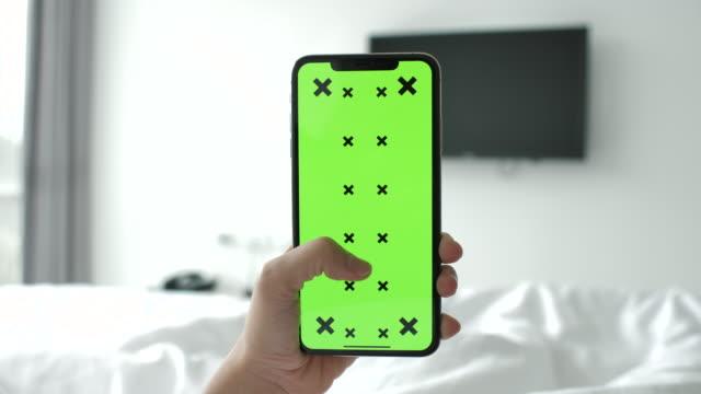 vídeos de stock, filmes e b-roll de jovem usando telefone com tela verde - portable information device