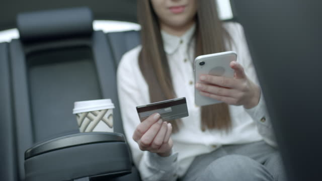 ms young woman using smart phone and credit card in back seat of crowdsourced taxi - passenger stock videos & royalty-free footage