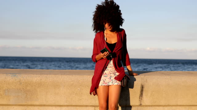 young woman using smart phone by the sea - hairstyle stock videos & royalty-free footage