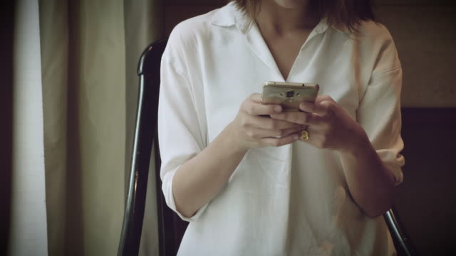 若い女性がカフェでスマート フォンを使用しています。 - accessibility点の映像素材/bロール