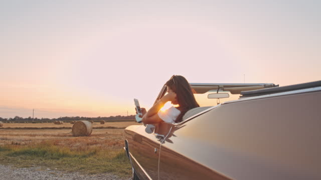 slo mo young woman using smart phone in convertible parked at rural, sunset roadside - fermo video stock e b–roll