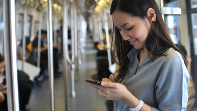 Young woman using smart phone on a train