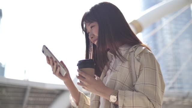 スマートフォンを使用する若い女性 - 興奮点の映像素材/bロール