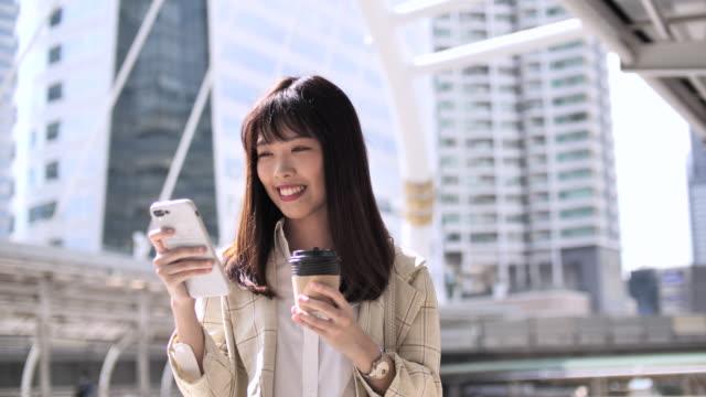 スマートフォンを使用する若い女性 - 手に持つ点の映像素材/bロール
