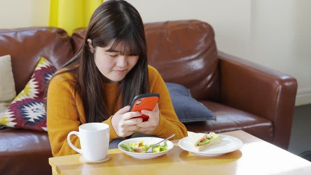 young woman using smart phone while having breakfast in living room at home - coffee table stock videos & royalty-free footage