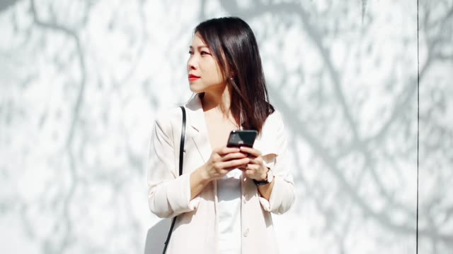 young woman using smart phone while walking on the street - over the shoulder stock videos & royalty-free footage