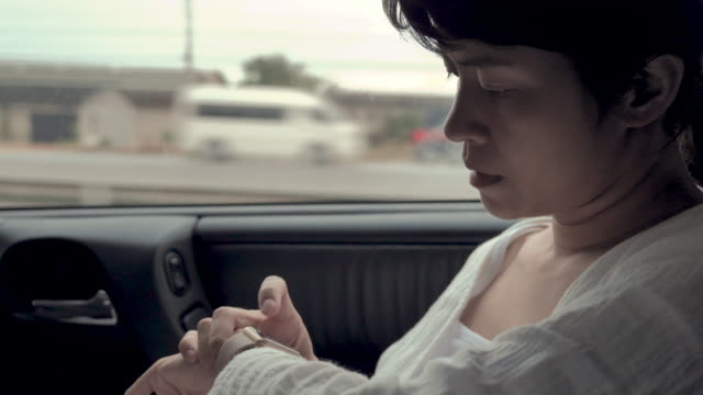 Young woman using smart watch in car.