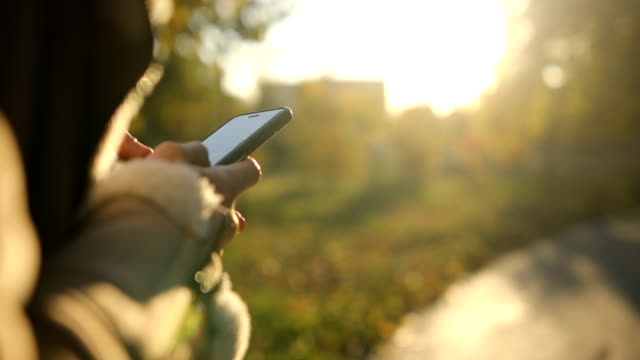 young woman using smartphone at sunset - back lit stock videos & royalty-free footage