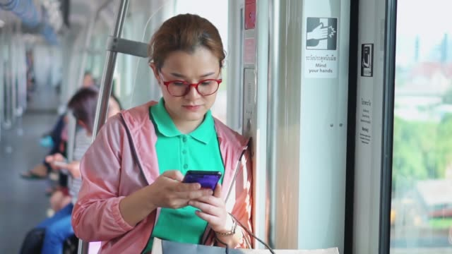 young woman using smartphone during metro ride,slow motion - public transport stock videos & royalty-free footage