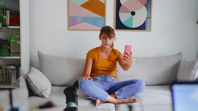 vidéos et rushes de jeune femme utilisant le smartphone pour l'appel vidéo - hot desking