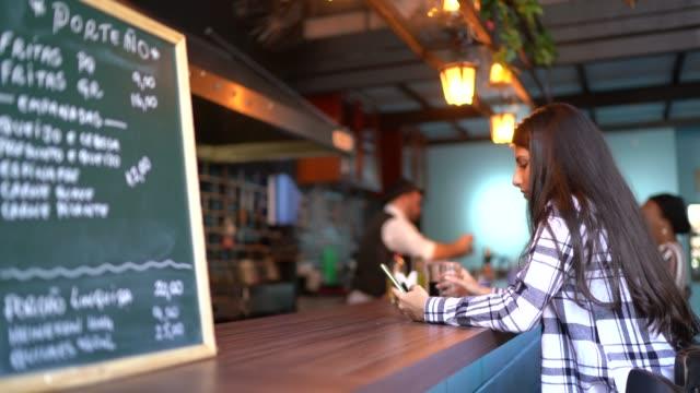 stockvideo's en b-roll-footage met jonge vrouw die smartphone in een staafteller gebruikt - internet surfen