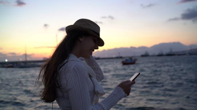 junge frau mit smartphone vor dem meer in mykonos, griechenland - nur junge frauen stock-videos und b-roll-filmmaterial