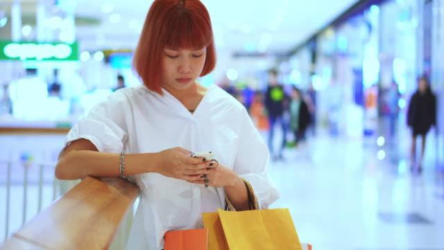 junge frau mit smartphone im einkaufszentrum - einkaufszentrum stock-videos und b-roll-filmmaterial