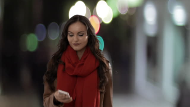 Young woman using smartphone in street at nigh texting and laughing