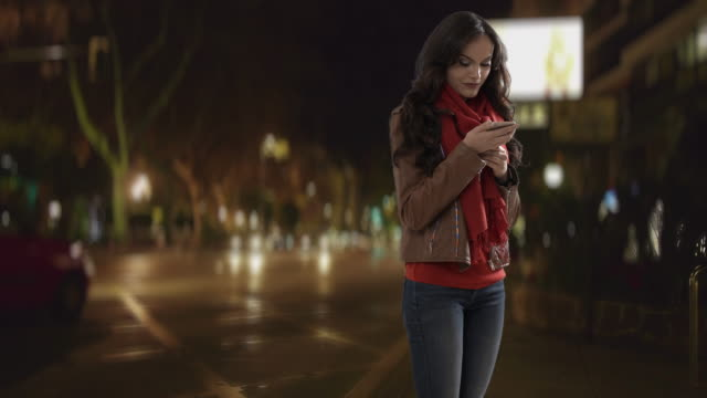 Young woman using smartphone in street at night, laughing and texting