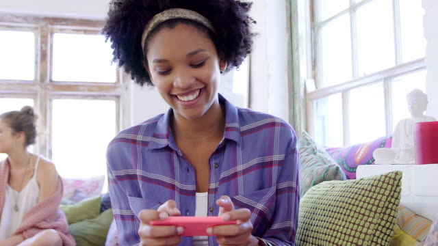 Young woman using smartphone  looking to camera and laughing