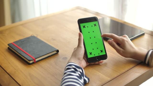 vídeos de stock, filmes e b-roll de jovem mulher usando smartphone com tela verde - rolando