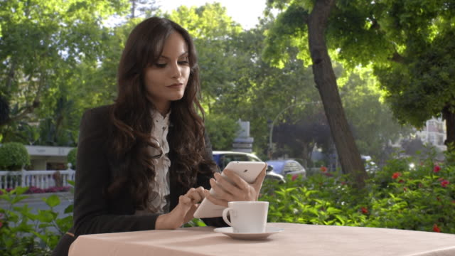 Young woman using tablet in café by street