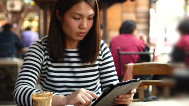 Young woman Using Tablet PC and Drinking Coffee in Cafe, 4k (UHD)