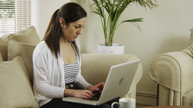 Young Woman using technology in her sitting room, type and sit back.