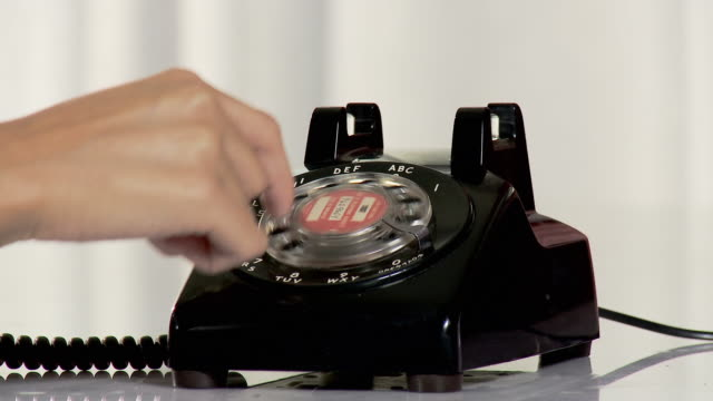 young woman using vintage dial phone - rotary phone stock videos and b-roll footage