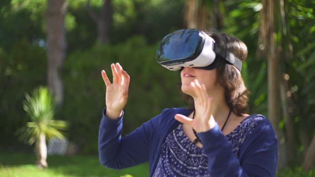 vídeos de stock e filmes b-roll de young woman using vr glass in her garden , moving her hands and smiling - só mulheres de idade mediana