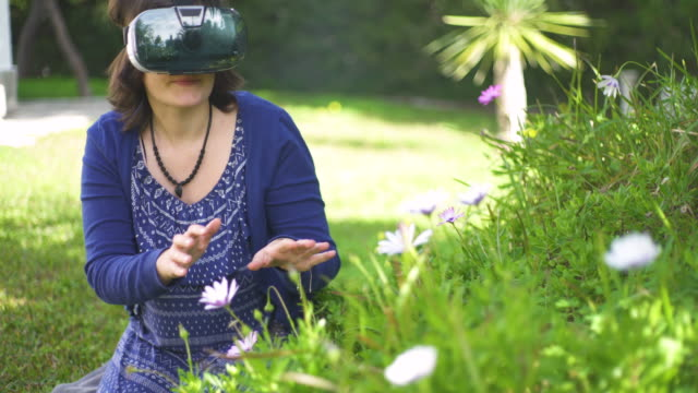 young woman using vr glass in her garden , moving her hands and smiling - silvestre stock-videos und b-roll-filmmaterial