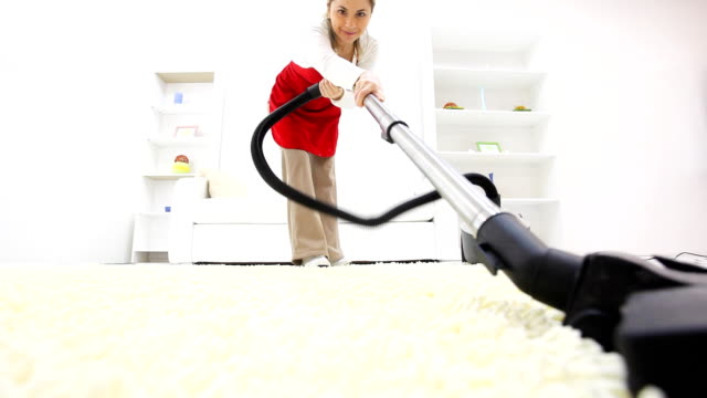 Young woman vacuuming her living room.