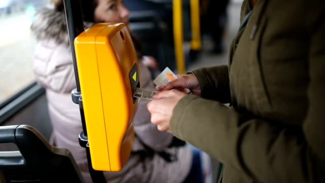 Young woman validating ticket in public transportation