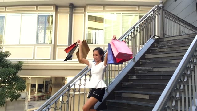 young woman very cheerful with shopping bags , slow motion